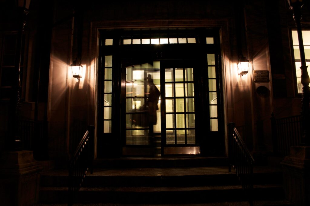 Exterior of building at night looking in lit doorway with blurred figure coming out of door.