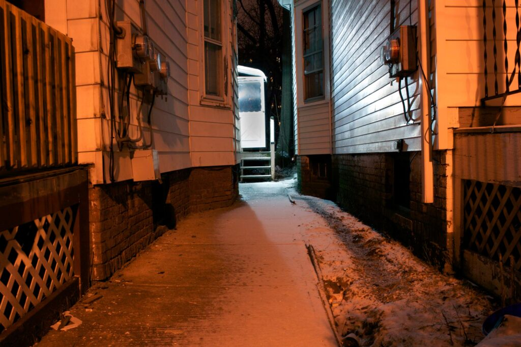 looking down an alley at night to a back door open on house - orange light glowing all around