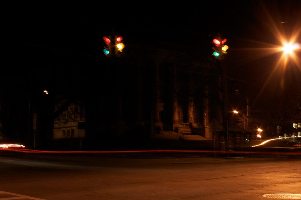 Night picture of stoplight with all lights showing in long exposure and car light streaks